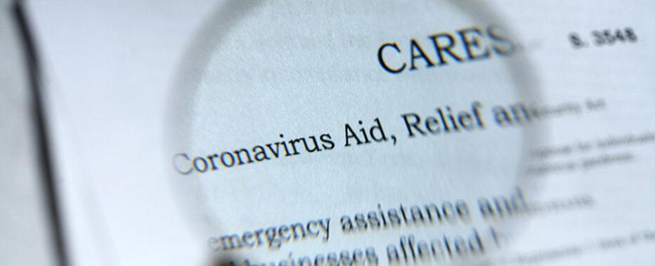 maginifying glass views coronavirus aid on paper
