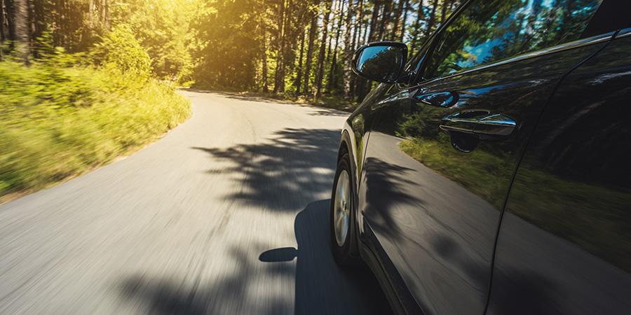 Featured Image of the driving assessment blog. A car driving along a forest road.