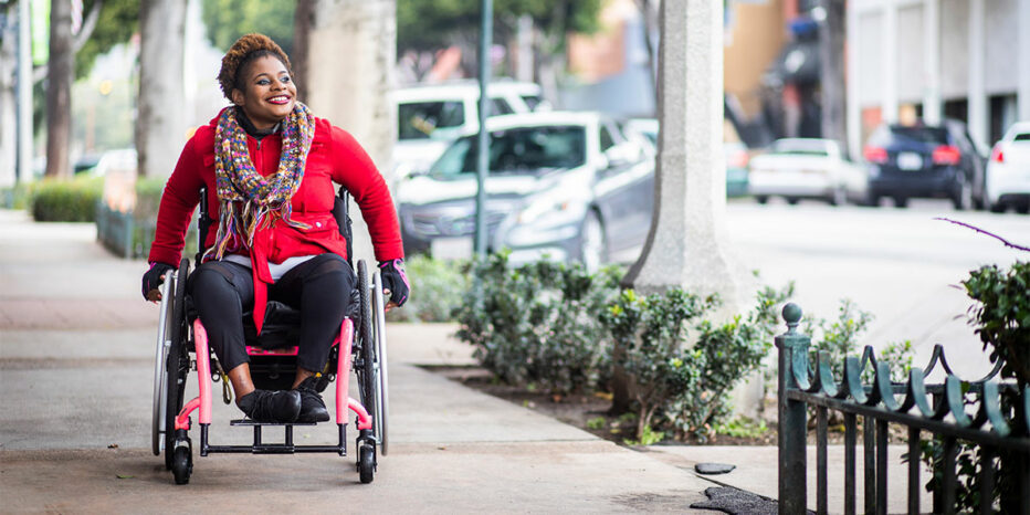 Smiling woman in wheelchair on the sidewalk of a city