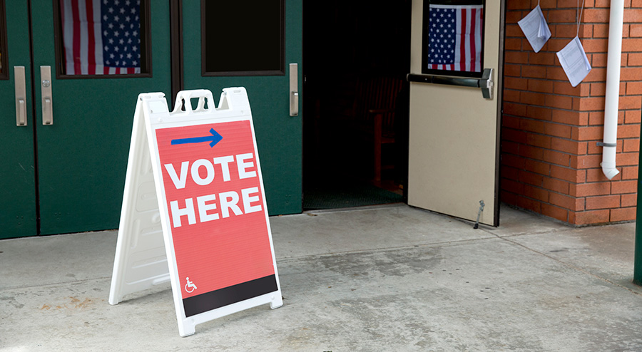 "Image of a polling place with a ""vote here"" sign out front"