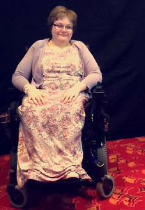 Stacy, wearing a floral dress, sitting in a wheelchair.