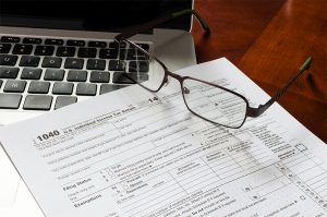 1040 income tax return form with MacBook and glasses