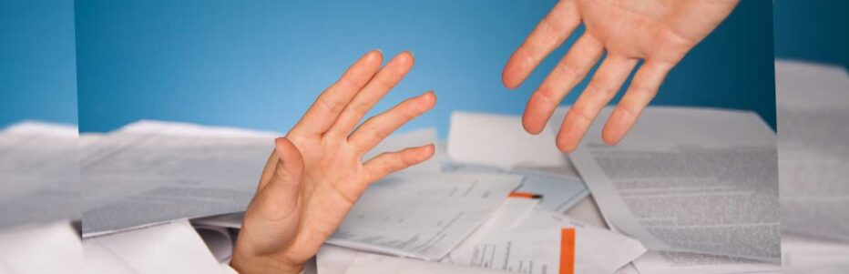 hand reaches out to hand coming out of pile of papers